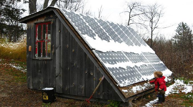nino-frente-a-un-panel-solar-en-la-nieve